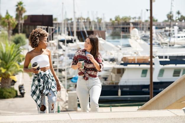 Donne che parlano bevendo caffè. due donne in posa nel porto turistico, yacht in background. ragazze che vanno in gita in barca sul mare