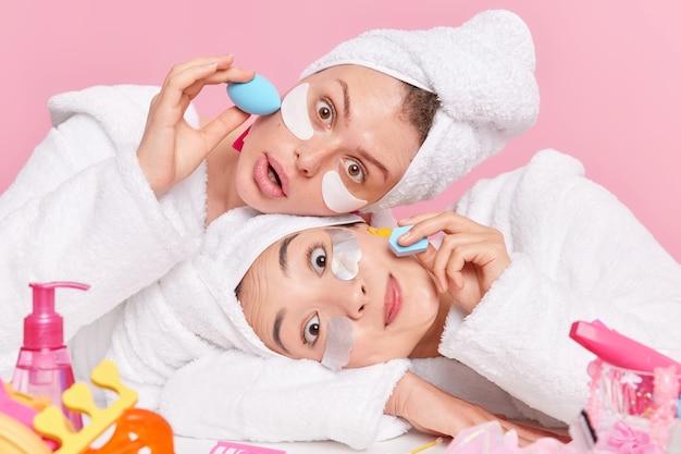 Le donne inclinano la testa applicano cerotti idratanti sotto gli occhi usano spugne cosmetiche per applicare fondotinta o cipria vestite con accappatoi bianchi asciugamani sulla testa