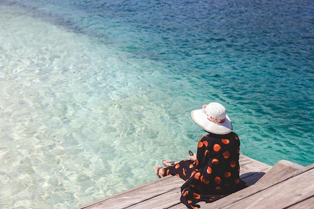 Turista delle donne in cappello estivo che tiene lo smartphone su una panca di legno sul mare a labuan bajo
