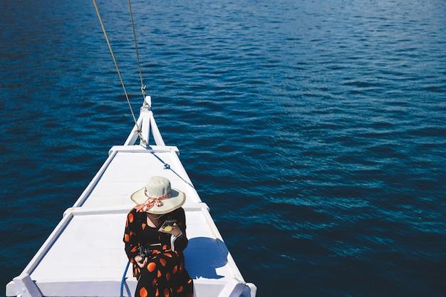 Turista delle donne in cappello estivo seduto sul ponte della barca godendosi il viaggio a labuan bajo