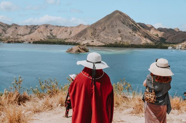Donne turiste in cappello estivo in piedi mentre guardano bellissimi paesaggi marini e colline a labuan bajo