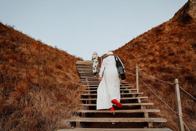 Turisti delle donne che camminano sulle scale di legno all'isola di padar labuan bajo