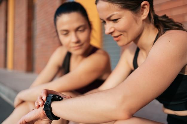 Donne che tengono traccia del tempo usando l'orologio da braccio. la sua amica attraente in attesa di risultati.