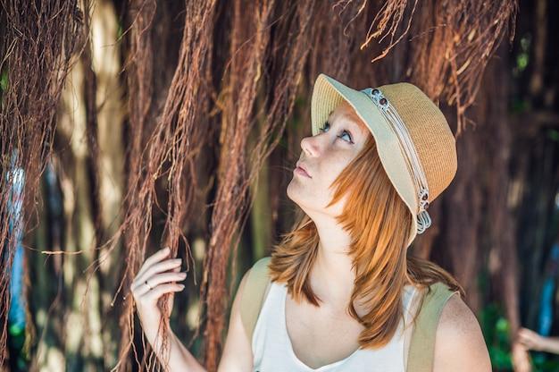 Le donne sul viaggiatore del vietnam sono sullo sfondo bellissimo albero con radici aeree