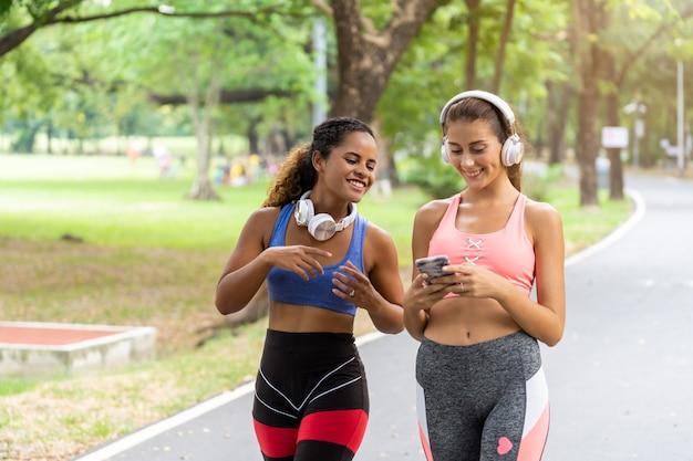 Donne che camminano e fanno jogging regolarmente per la salute nel parco e ascoltano musica rilassante.