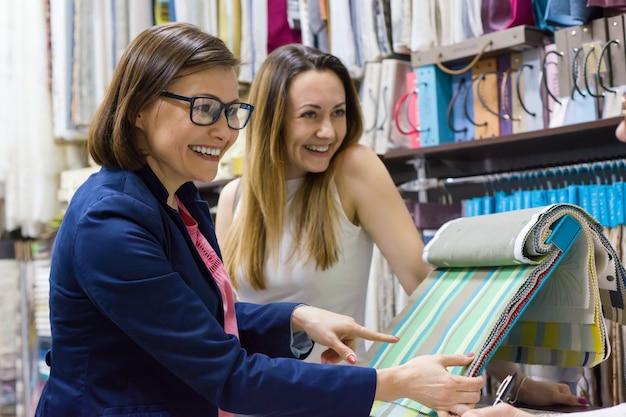 Le donne guardano campioni di tessuti per tende