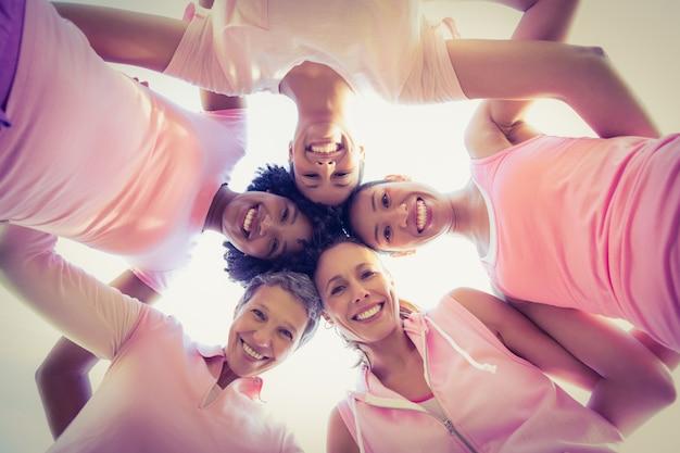 Donne che indossano rosa per il cancro al seno con le braccia intorno