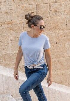 Donne che indossano t-shirt, jeans e occhiali da sole che salgono le scale e si guardano indietro all'aperto in una soleggiata giornata estiva