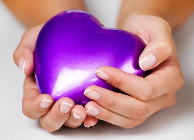 Donne con french manicure che tengono il cuore nelle mani
