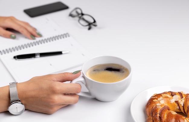 Le donne con le mani ben curate con il design delle unghie verde primavera estate tengono la tazza di caffè