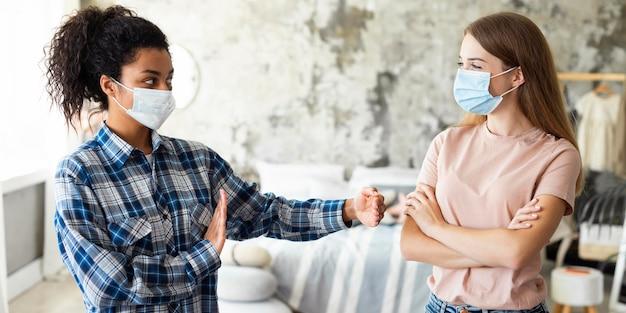 Donne con maschere mediche che mantengono le distanze sociali