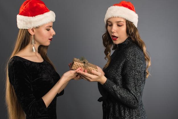 Donne con cappelli di babbo natale che si scambiano doni