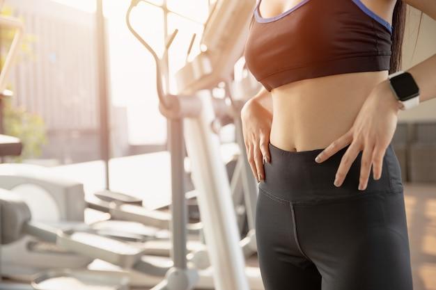 Le donne con i muscoli addominali addominali sottili si adattano e sono fermi nell'abbigliamento sportivo in palestra
