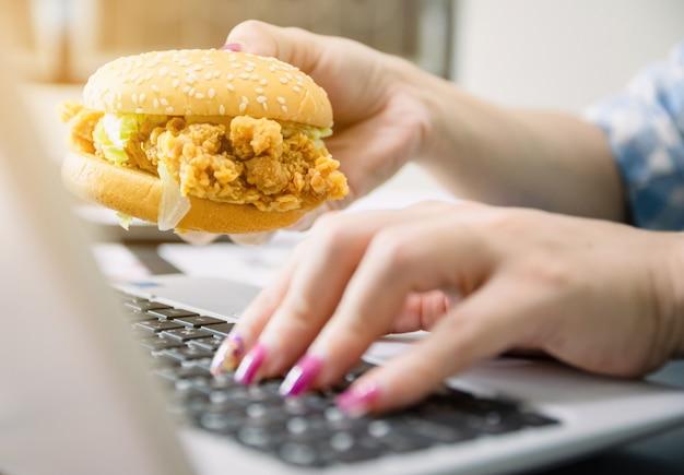 Le donne lavorano e mangiano hamburger per pranzare in ufficio