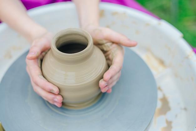 Donne che lavorano al tornio del vasaio. le mani scolpiscono una tazza da una pentola di terracotta. laboratorio di modellazione al tornio da vasaio.
