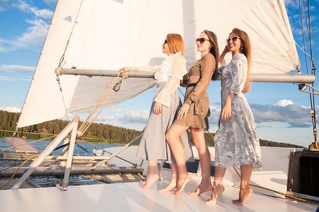 Donne su uno yacht contro uno sfondo di vele bianche e concetto di viaggio in barca del cielo blu