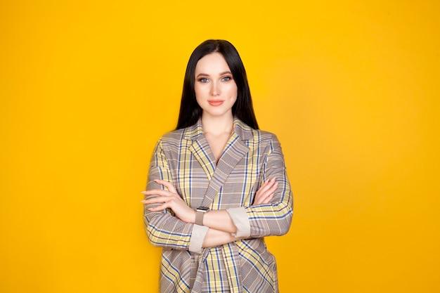 Donne su sfondo giallo, le mani giunte davanti a lei. il concetto di imprenditrice o pianificazione, formazione, lavoro femminile.