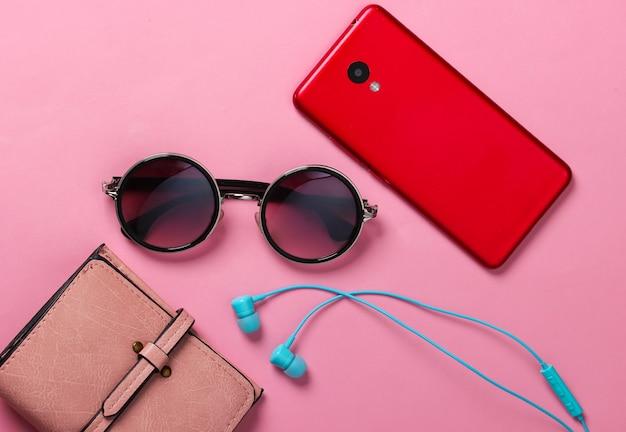 Accessori e gadget delle donne su un giallo. auricolari, eleganti occhiali da sole rotondi, smartphone, portafoglio in rosa