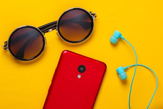 Accessori e gadget delle donne su un giallo. auricolari, eleganti occhiali da sole rotondi, smartphone su un giallo