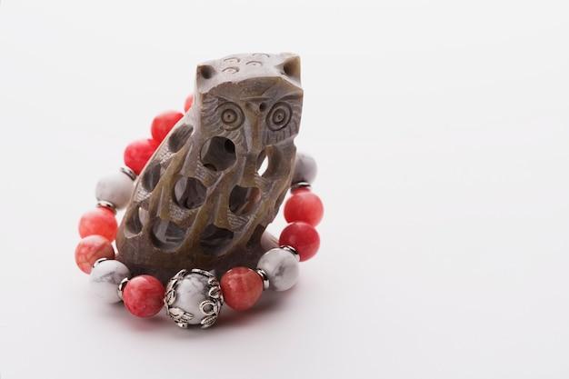 Braccialetto da donna in corallo e pietra di luna su un gufo di pietra