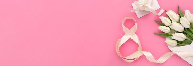 Bandiera della decorazione festiva del giorno delle donne, sulla busta bianca del fondo rosa con i tulipani e il nastro a forma di numero otto