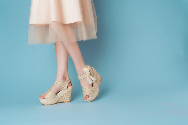 I piedi delle donne vestono scarpe scarpe sfondo blu