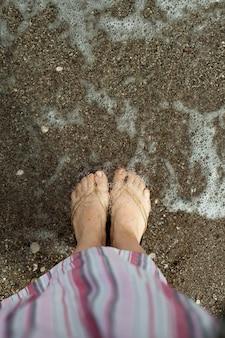 I piedi delle donne si rilassano sulla sabbia nell'acqua di mare una donna con un vestito rosa a righe un viaggio e uno stile di vita su...