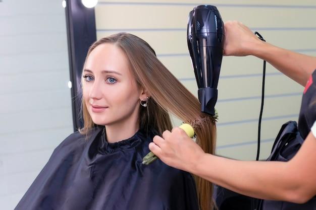 Parrucchiere da donna, salone di bellezza. asciugare i capelli con un asciugacapelli e una spazzola rotonda.