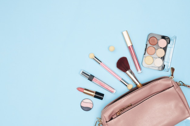 Borsa da donna con cosmetici, strumenti per il trucco e accessori su uno sfondo blu, bellezza, moda, concetto di acquisto, piatto lay. foto di alta qualità