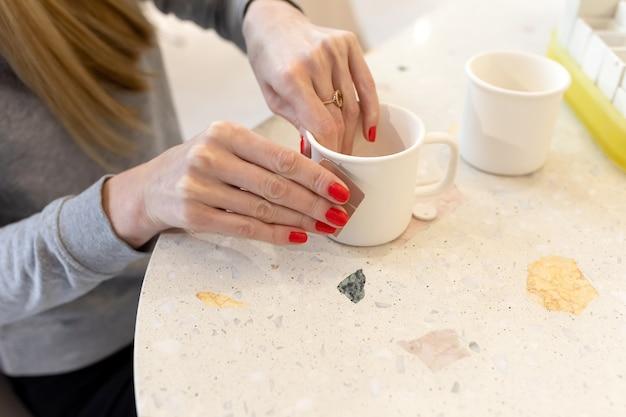 Le mani delle donne puliscono la tazza di argilla bianca con carta vetrata prima di applicarvi un motivo in officina