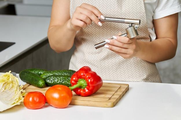 Le mani delle donne tengono in mano uno spremiaglio processo di cucinare qualcosa di delizioso