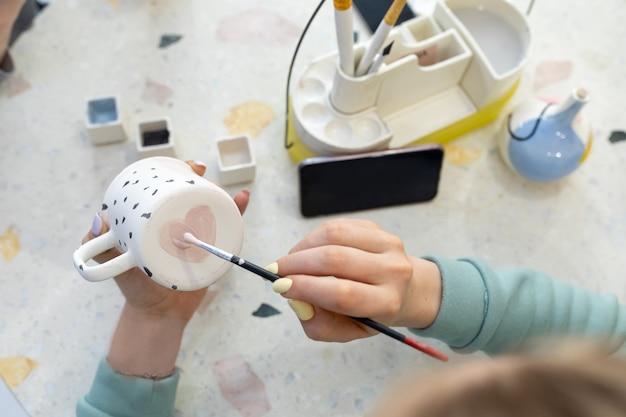 Le mani delle donne dipingono un cuore rosa sul retro di una tazza di ceramica con un pennello