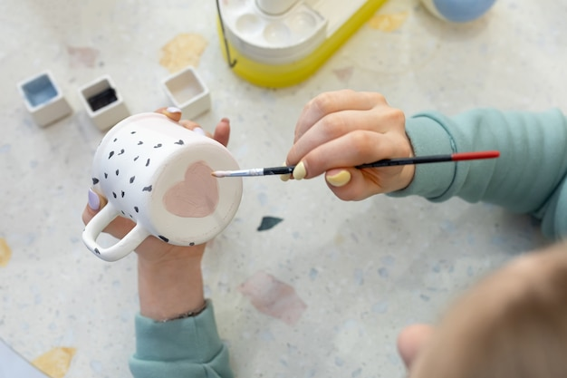 Le mani delle donne dipingono un cuore rosa sul retro di una tazza di ceramica