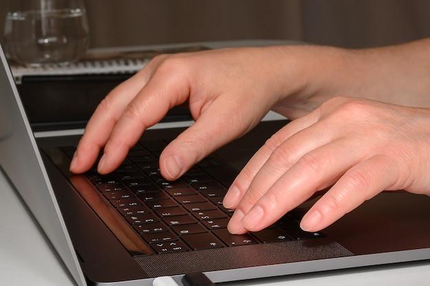 Le mani delle donne che stampano su un laptop