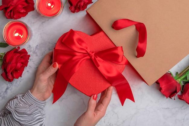 Le mani delle donne toccano un fiocco di raso rosso su una confezione regalo di cartone a forma di cuore