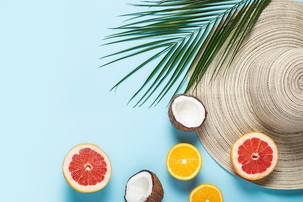 Cappello da donna con tesa larga, frutti tropicali e un ramo di una palma su sfondo blu.