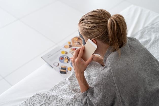 La salute delle donne. terme e benessere. donna con maschera facciale che si rilassa sdraiata sul letto leggendo una rivista che ordina cibo al telefono