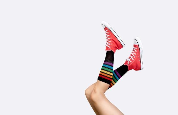 Gambe delle donne in eleganti scarpe da ginnastica rosse e calzini arcobaleno sulla superficie grigia