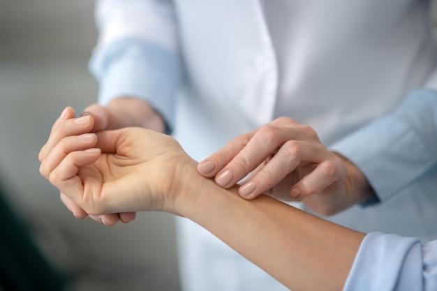 Le mani del medico esperte e pulite delle donne palpano delicatamente l'avambraccio del paziente, trovando l'area dolorante