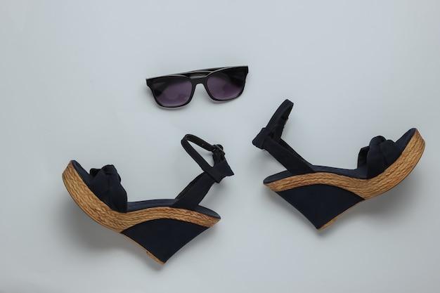 Sandali da donna con occhiali da sole piattaforma su sfondo bianco scarpe estive da donna e accessori