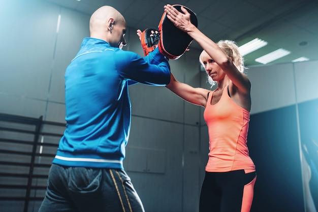 Allenamento di autodifesa femminile con personal trainer, allenamento di combattimento in palestra, arti marziali