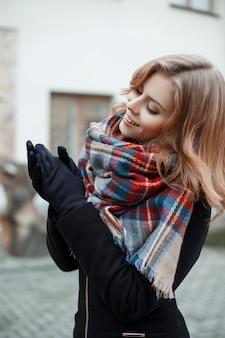 Meravigliosa giovane donna attraente in un elegante cappotto nero con una calda sciarpa di lana in guanti neri si pone il giorno d'autunno strada
