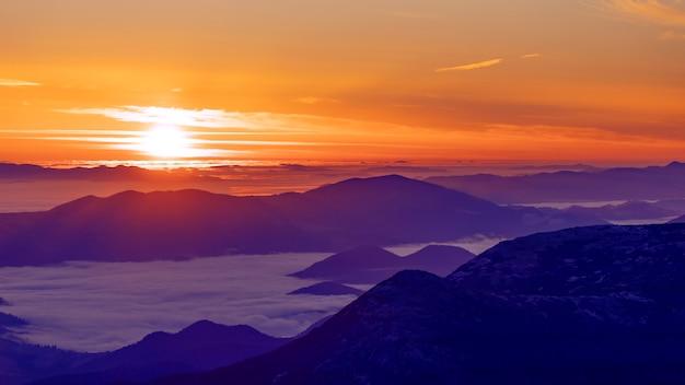 Meraviglioso paesaggio di montagna autunnale. alba con nebbia negli intermontani.