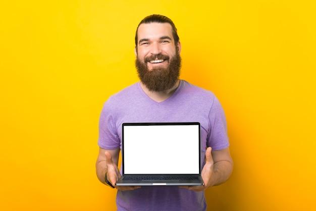Meraviglioso uomo barbuto sta tenendo un laptop con schermo vuoto davanti alla telecamera.