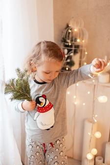 Meravigliosa bellissima bambina in pigiama alla moda con luci e rami di albero di natale
