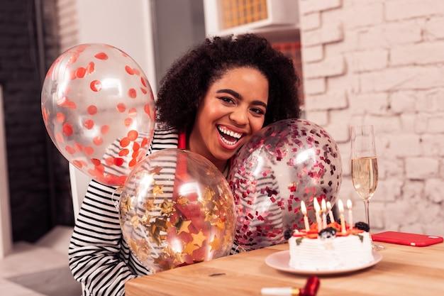 Meravigliosa festa di compleanno. felice bella donna in possesso di palloncini pur avendo una grande festa