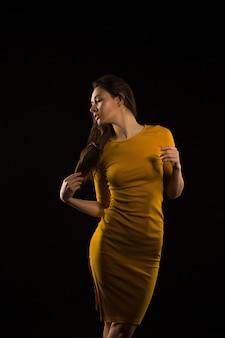 Meravigliosa donna bruna con i capelli lunghi in posa in abito giallo nell'ombra