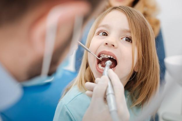 Meraviglioso medico pediatra competente che risolve alcuni problemi con i suoi piccoli pazienti denti mentre lei gli fa una visita regolare e si siede con la bocca aperta