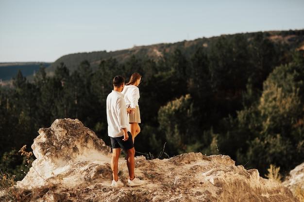 Coppie meravigliose che tengono le mani stanno camminando lungo la montagna rocciosa