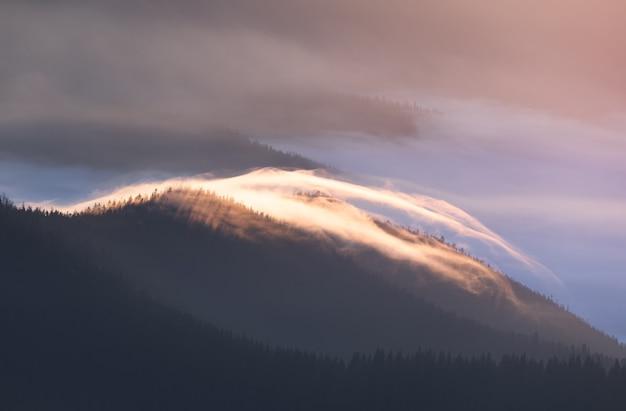 Meravigliosa alba in montagna. nebbia in cima.